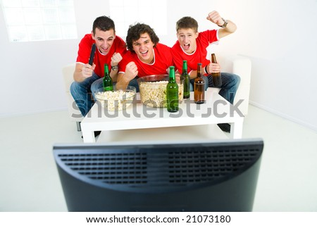 Three happy men sitting on couch and watching sport on TV. Front view. - stock photo