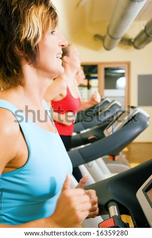 Three happy people running on a treadmill in a gym, a mature woman in the front, younger couple in the background - stock photo