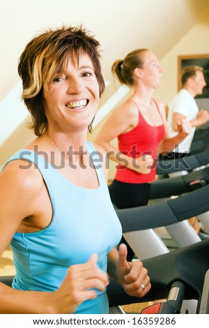 Three happy people running on a treadmill in a gym; slight motion blur on woman in foreground for a dynamic picture - stock photo