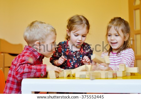 three happy prescholler children with wooden blocks