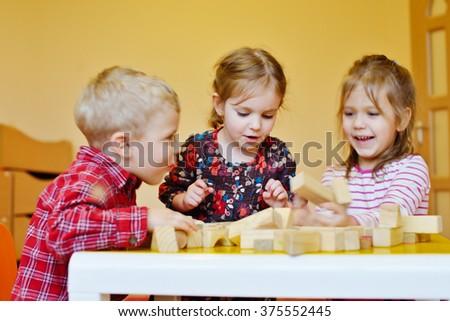 three happy prescholler children with wooden blocks - stock photo