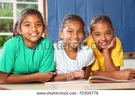 Three happy school girls reading a book in class