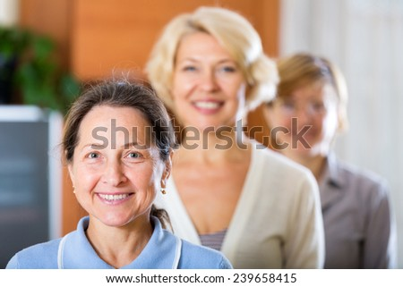 three happy senior mature women posing at home interior - stock photo