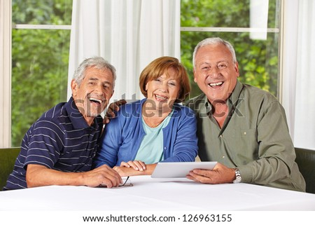Three happy senior people with tablet computer in a retirement home - stock photo