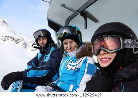Three happy skiers in helmets and sport suits ride on funicular in mountains. Focus on woman. - stock photo