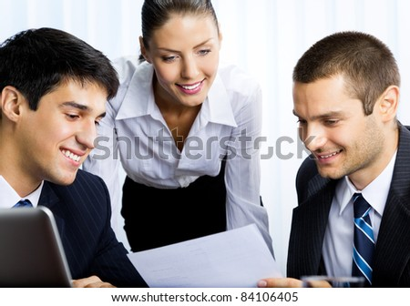 Three happy smiling business people working with document at office - stock photo