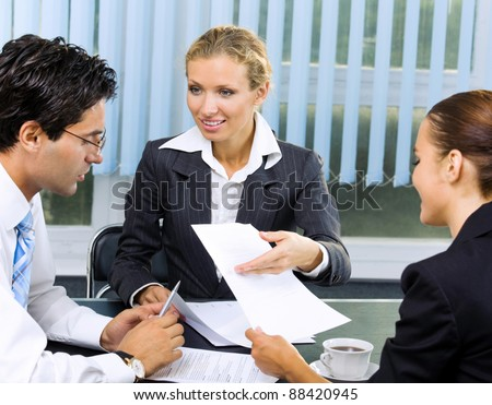Three happy smiling business people working with document at office