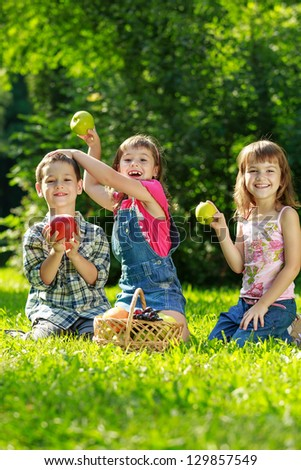 Three happy smiling child playing in park - stock photo