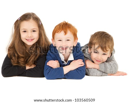 Three happy smiling children laying together in group on floor. Isolated on white.