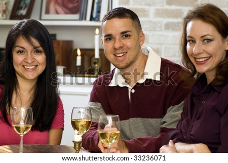 Three happy, smiling friends enjoying wine and each other's company. - stock photo