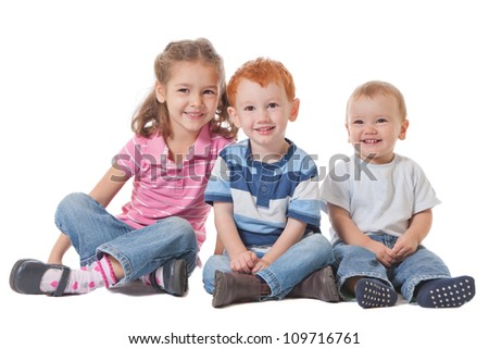 Three happy smiling kids sitting on the ground - stock photo