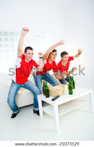 Three happy sport's fans get up from couch with raised hands. - stock photo