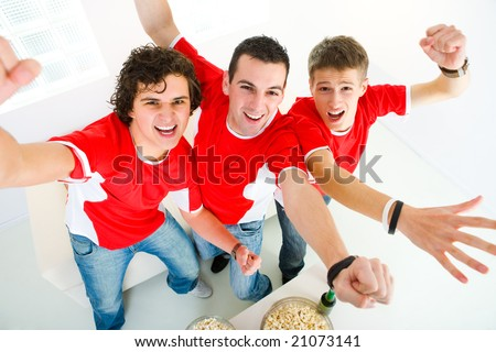 Three happy sport's fans get up from couch with raised hands. They looking at camera. High angle view.
