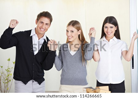 Three happy students holding their hands and cheering in university - stock photo