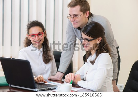 Three happy successful business people working with laptop at office  - stock photo