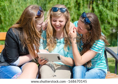 Three happy teen girl friends and tablet computer - stock photo