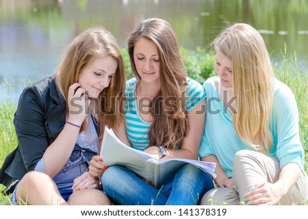 Three happy teen girl friends reading school book on bright summer day outdoors