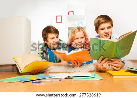 Three happy teen kids read books doing homework