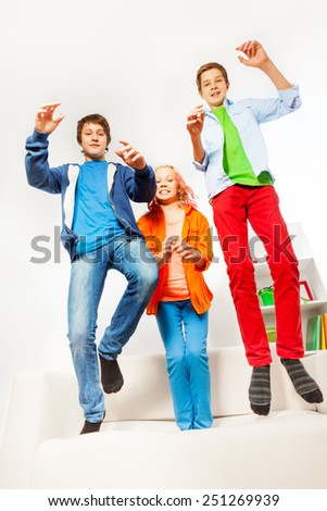 Three happy teenagers jumping on white sofa - stock photo