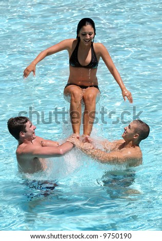 Three happy teenagers playing in the pool - stock photo