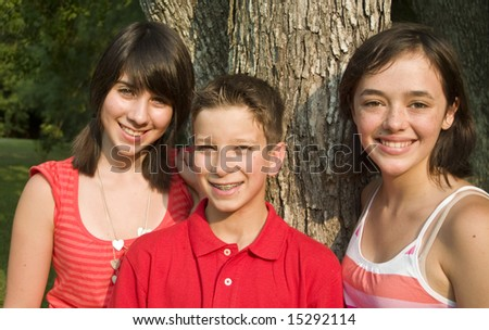 Three happy teens or pre-teens standing by a tree in the late afternoon sun.