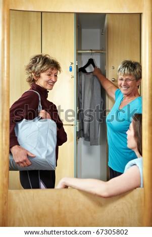 Three happy woman chatting in locker room - stock photo
