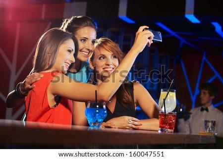 Three happy women at an nightclub party taking a self-portrait - stock photo