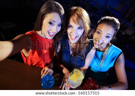 Three happy women at an nightclub party taking a self-portrait - stock photo