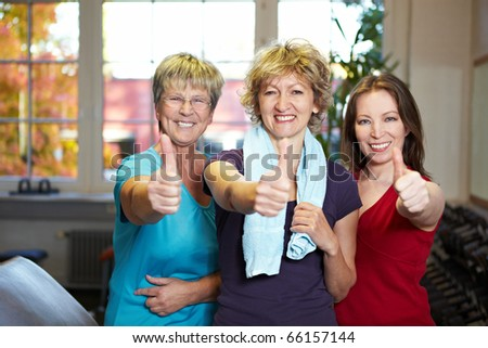 Three happy women holding thumbs up in gym - stock photo