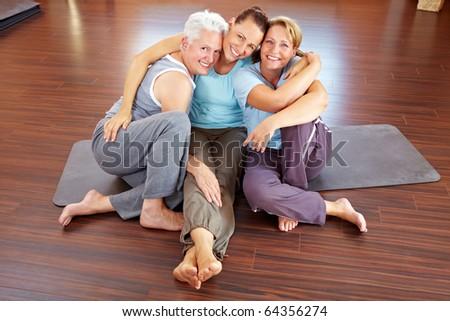Three happy women sitting in a gym - stock photo
