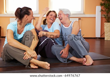 Three happy women sitting in a gym