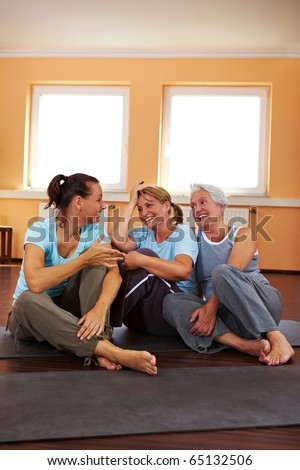 Three happy women sitting in a gym and talking - stock photo