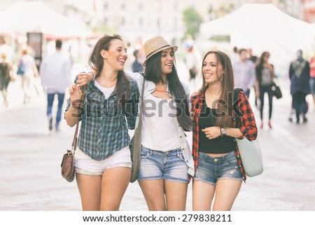 Three happy women walking in the city, talking each other and smiling. This is a mixed race group, one girl is half asian and one is middle eastern. Lifestyle, friendship and urban life concepts. - stock photo