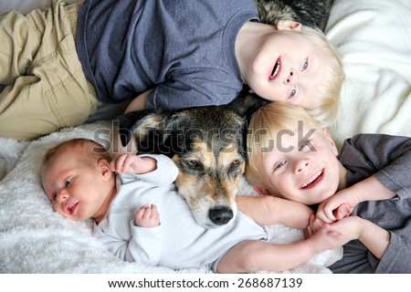 Three happy young children, including a newborn baby girl, a toddler, and their big brother are laying in bed snuggling with their pet dog. - stock photo