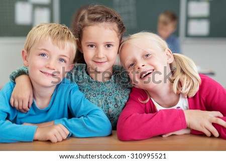 Three happy young friends in kindergarten with a young girl in the centre standing with her arms around the shoulders of a boy and girl as they smile at the camera