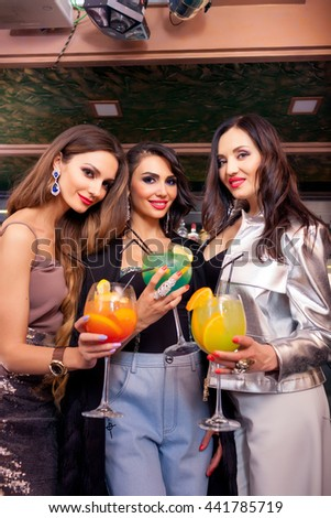 Three happy young girl friends having fun in a bar drinking cocktails - stock photo