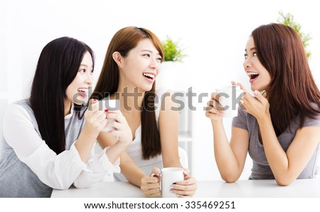three happy young woman chatting in living room - stock photo