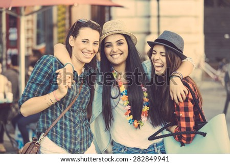Three happy young women in the city, talking each other and smiling. This is a mixed race group, one girl is half asian and one is middle eastern. Lifestyle, friendship and urban life concepts. - stock photo