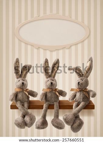 Three hares sitting on the shelf - stock photo