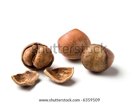 three hazelnuts, one of them already cracked, isolated on white