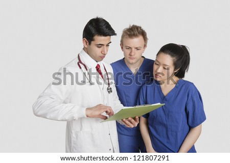 Three healthcare professional discussing medical report over gray background - stock photo