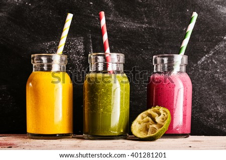 Three healthy fresh fruit and vegetable smoothies, with mango, kale and raspberry, blended with yogurt and served in small mason jars on a rustic table - stock photo