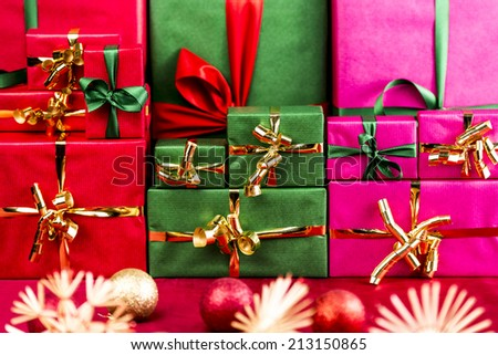 Three heaps of wrapped gifts sorted by color. Red, green and magenta. All plain-colored with monochrome ribbons and bows. Tightly-framed, shallow DOF. Christmas bulbs and stars on red cloth in front. - stock photo