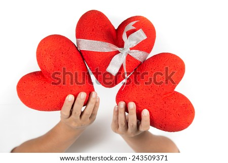 Three hearts, hands, gray background. - stock photo