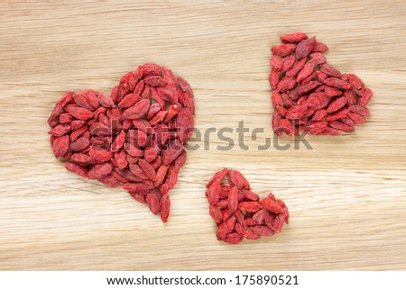 three hearts made of goji berries on wooden surface - stock photo