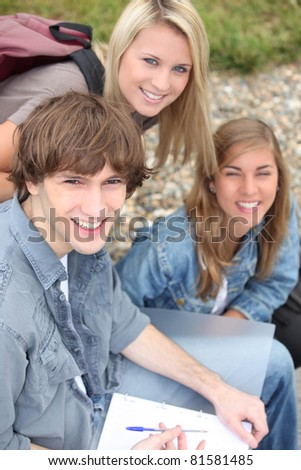 Three high school friends outdoors - stock photo