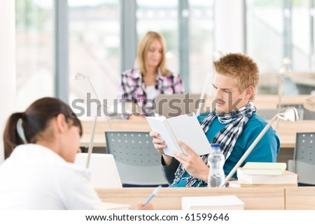 Three high school students in classroom studying with books and laptop