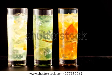 Three highball glasses filled with alcoholic or non-alcoholic cocktail drinks mixed with ice and tropical fresh fruits as lemon, lime and orange, on a table, close-up with copy space on black - stock photo