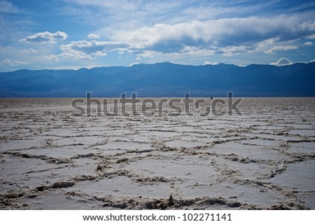 Three hikers walk across the vastness of Death Valley National Park. - stock photo