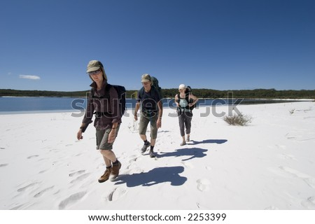 Three hikers walking on a beach in australia on fraser island on a clear sunny day 1 - stock photo